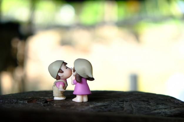 Bambole sveglie delle coppie che baciano sui bastoni di legno