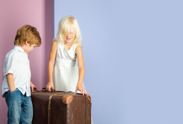 Coppia carina di bambini con la valigia. concetto di amicizia.