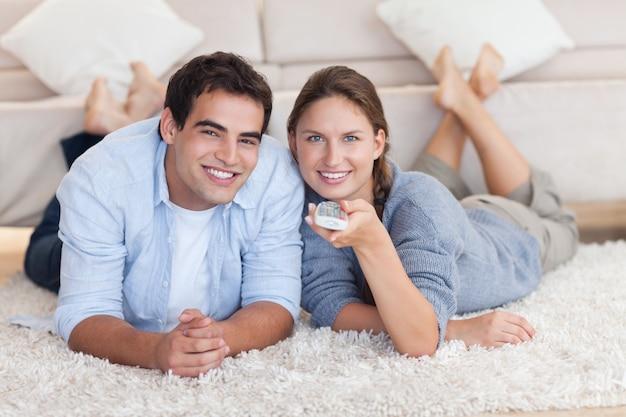 Coppie sveglie che guardano tv mentre trovandosi su un tappeto