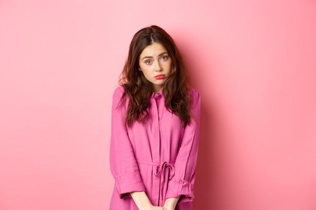 Ragazza carina timida che fa una faccia stupida, vuole qualcosa, implorando un regalo, in piedi contro il muro rosa. copia spazio