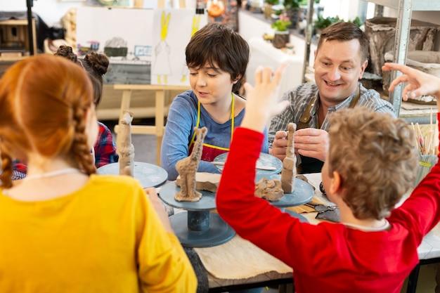 Simpatici bambini creativi che si sentono incredibili avendo lezione d'arte con l'argilla