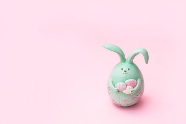 Coniglietto di pasqua creativo sveglio della foto che tiene le uova su fondo rosa con lo spazio della copia