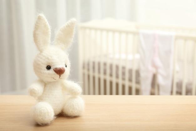 Simpatico giocattolo per bambini coniglietto all'uncinetto sul tavolo in camera da letto
