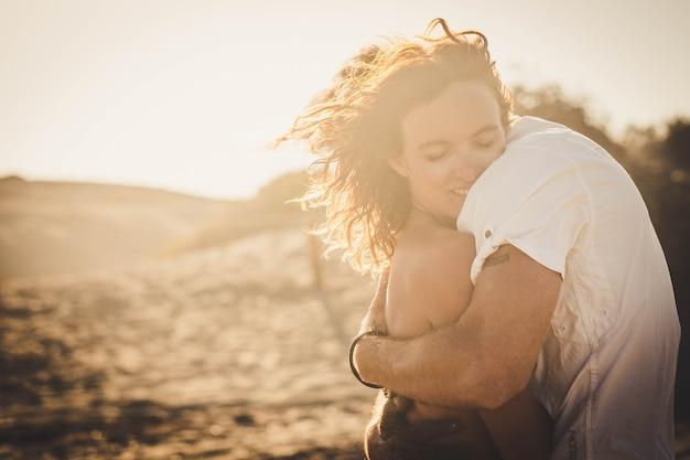 Carino coppia di due adulti abbracciati e innamorati insieme - donna con gli occhi chiusi che abbraccia il suo ragazzo