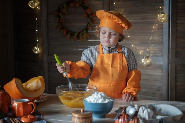 Il simpatico ragazzo dai capelli ricci in un costume da cuoco arancione sta preparando la torta di zucca per il ringraziamento. tradizioni di vacanza in famiglia