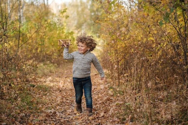 Ragazzo dai capelli ricci sveglio che gioca con l'aereo di legno nella sosta di autunno