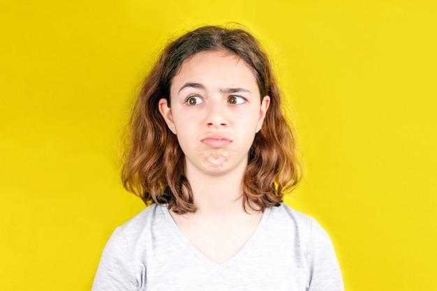 Ragazza carina riccia dell'adolescente con la faccia buffa. sorpresa e shock