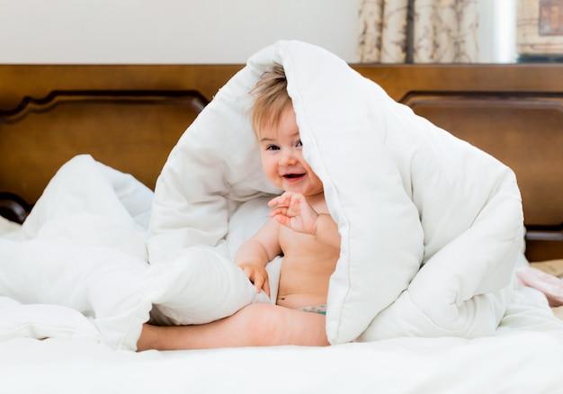 Un bambino carino e carino sorride sotto una coperta bianca. ritratto di bambino di 11 mesi