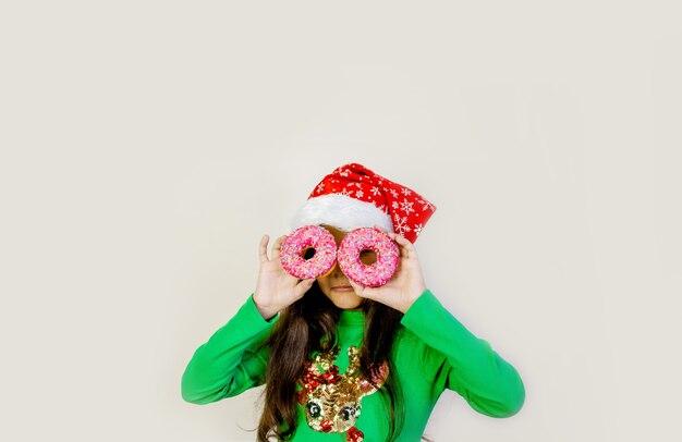 Ragazza carina capelli scuri in cappello della santa sorridente, divertendosi e guardando attraverso due ciambelle sui suoi occhi.