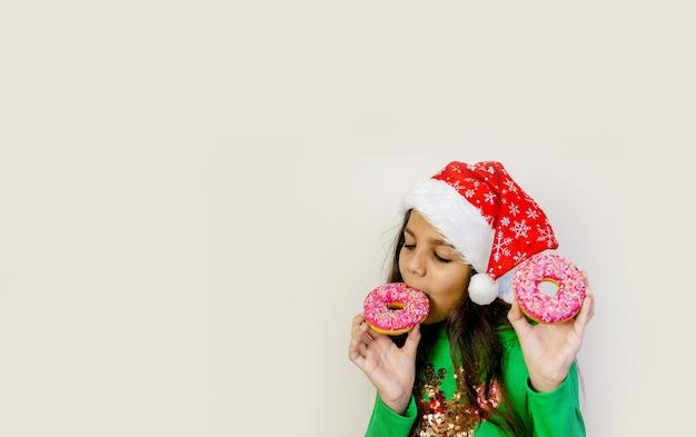 Ragazza carina capelli scuri con cappello santa sorridente, divertirsi e assaggiare due ciambelle sugli occhi.