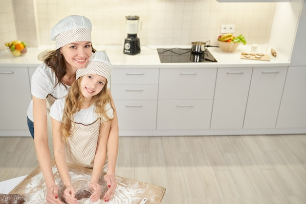 Figlia e madre sveglie in grembiuli che cuociono i biscotti alla cucina