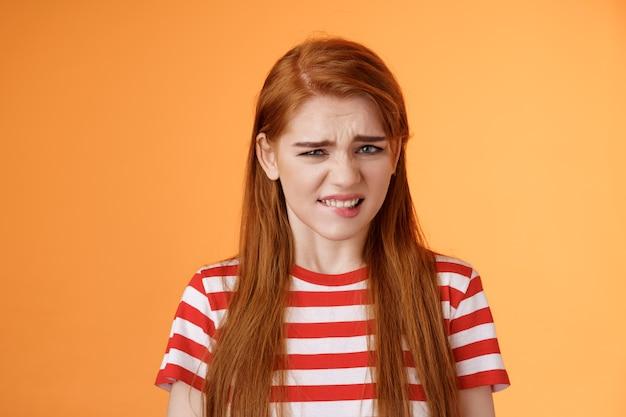 Carina ragazza rossa disgustata rabbrividisce per l'avversione, cattivo odore, smorfia accigliata delusa, stringere i denti infastiditi, esprimere antipatia e riluttanza, sentirsi male insoddisfatti, rifiutare l'offerta