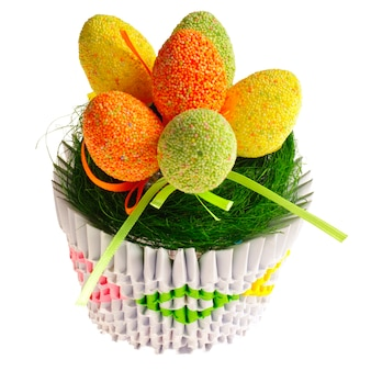 Uova di pasqua sveglie sull'erba decorativa nel cestino di origami. isolato su sfondo bianco