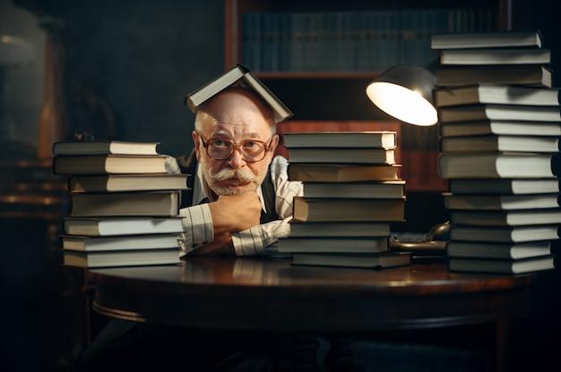 Scrittore anziano carino seduto al tavolo con una pila di libri in ufficio a casa. il vecchio con gli occhiali scrive un romanzo di letteratura in una stanza con fumo, ispirazione