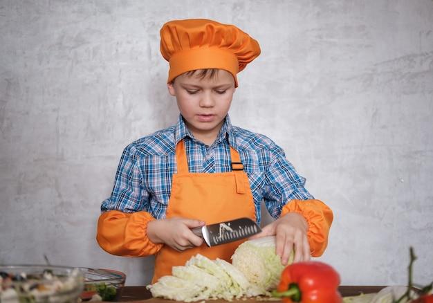 Il ragazzo europeo sveglio taglia il cavolo cinese con il coltello sul tagliere per insalata di verdure