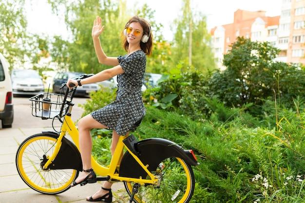 Ragazza europea carina cavalca una bici a noleggio in un parco cittadino