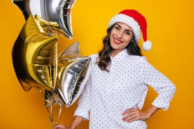 Carina giovane donna eccitata con un cappello da babbo natale rosso con palloncini di elio d'aria in posa sullo sfondo giallo isolato mentre celebra un natale e un nuovo anno