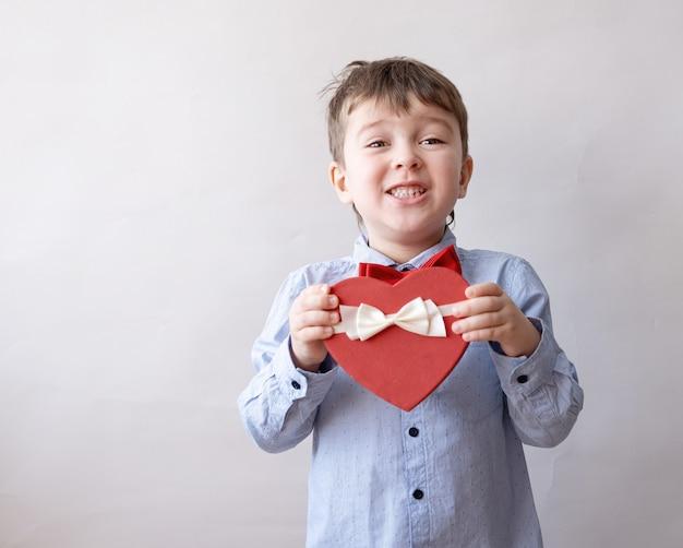 Piccolo ragazzo caucasico uscito sveglio in farfallino con il nastro bianco del contenitore di regalo del cuore rosso. giorno di san valentino.