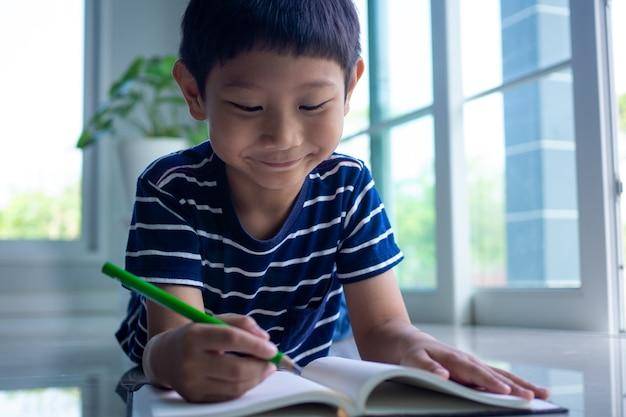 Il viso carino di uno studente asiatico maschio sta imparando e facendo i compiti allegramente nel soggiorno di casa. concetto di studio