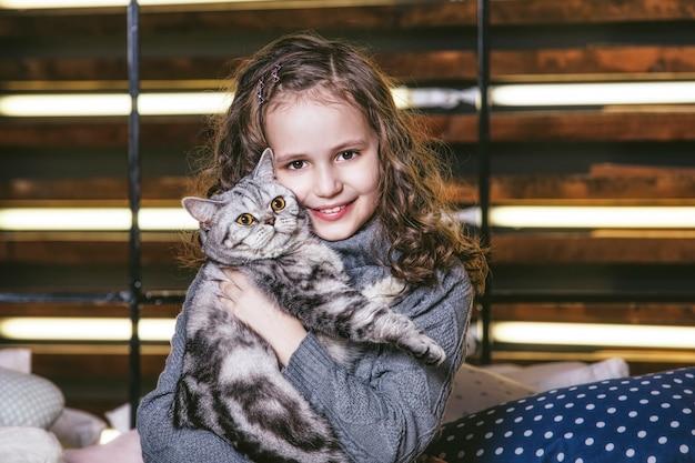 Bambina carina moda con un gattino britannico tra le braccia di molto felici insieme