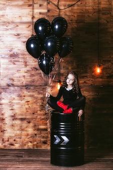 Bambina carina di moda con un mazzo di palloncini neri contro il muro con lampade