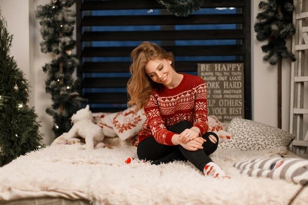 La bella donna alla moda sveglia con un'acconciatura in un maglione alla moda si siede su un letto