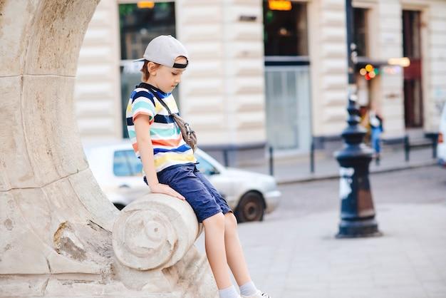 Ragazzo alla moda carino che cammina per la città. bambino felice che indossa abiti casual alla moda e marsupio. moda estiva. ragazzo bello alla moda che gode delle vacanze estive. infanzia felice.