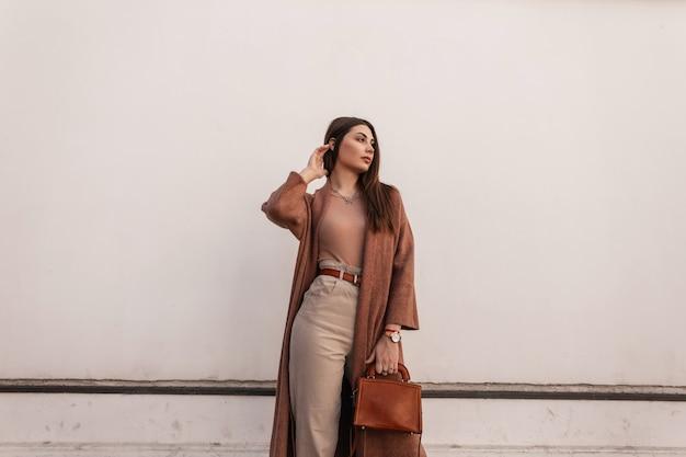 Carina giovane donna alla moda in elegante cappotto in pantaloni con borsa marrone elegante in pelle in posa vicino all'edificio bianco vintage sulla strada. la ragazza attraente urbana riposa all'aperto. outfit casual alla moda primaverile