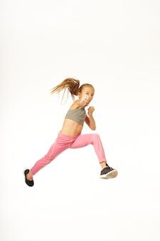 Carino bambino femminile in abbigliamento sportivo facendo posizione di combattimento e urlando mentre salta in studio. isolato su sfondo bianco