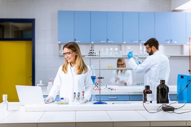 Ricercatore femminile carino in camice bianco e maschera protettiva utilizzando laptop mentre si lavora in laboratorio
