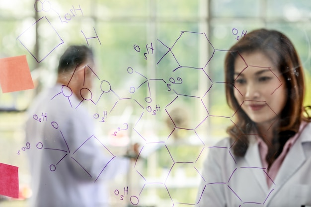 Simpatica scienziata con pennarello che scrive formule chimiche su una lavagna di vetro mentre lavora con i colleghi in laboratorio.
