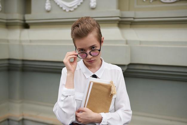 Studentessa carina con libro in mano bicchieri edificio retrò istituto di istruzione