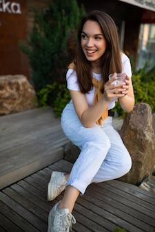 La giovane donna sveglia libera gode del caffè mentre si siede in un bellissimo parco estivo sulla pietra.