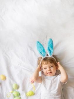 Bambino divertente sveglio con le orecchie del coniglietto e le uova di pasqua colorate a casa su una priorità bassa bianca