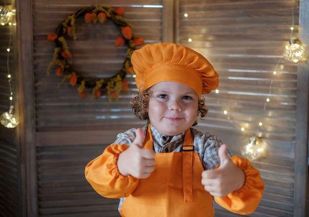 Il ragazzo divertente sveglio in un costume dello chef mostra un gesto simile. piccolo chef in cucina