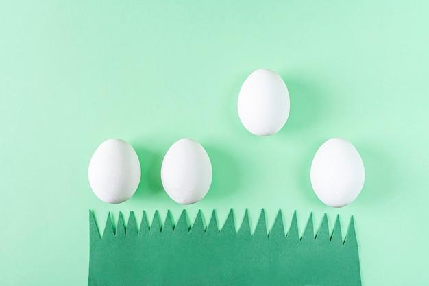 Composizione di pasqua creativa divertente sveglia con erba di carta verde e uova bianche. creatività fai da te e per bambini. artigianato fatto in casa.