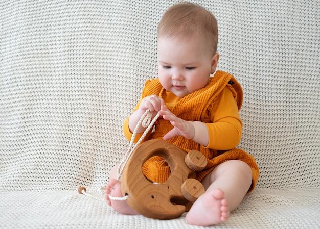 Piccola neonata caucasica divertente sveglia che gioca con il giocattolo di legno dell'elefante. giocattoli per bambini piccoli. sviluppo iniziale