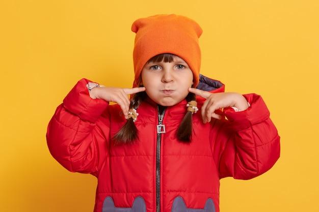 Ragazza carina bambino divertente in protezione arancione e giacca rossa scherzare sulla parete gialla