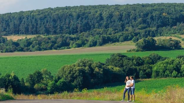 Coppie gentili sveglie che camminano nel prato verde sul fondo della foresta. il ragazzo abbraccia la ragazza.