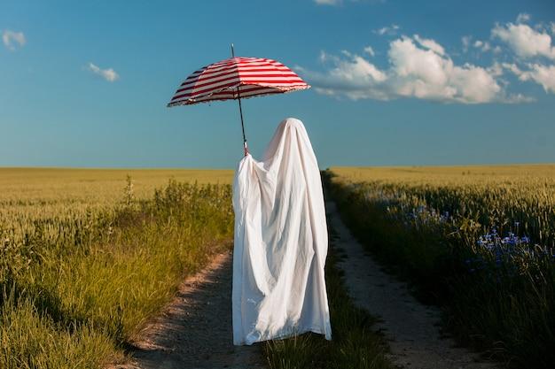 Fantasma carino in un lenzuolo con l'ombrello sulla strada di campagna vicino a un campo di grano