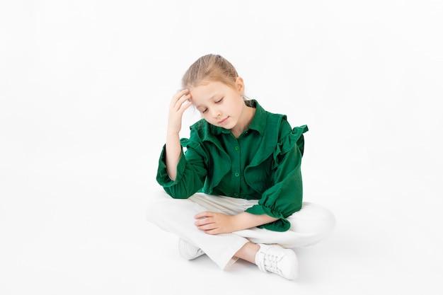 Ragazza carina 7-9 anni seduto su un bianco