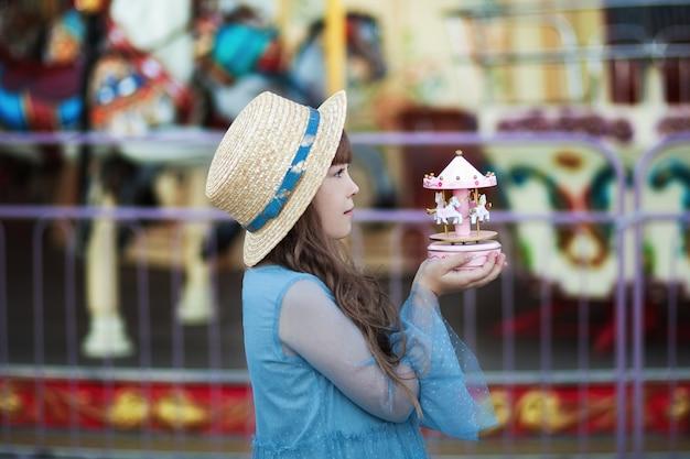 Ragazza carina nel parco divertimenti giostra giocattolo vintage nelle mani di una bambina con cappello
