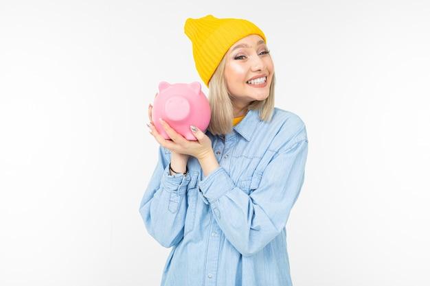 Ragazza carina in una camicia blu con una banca per risparmiare spazio copia denaro