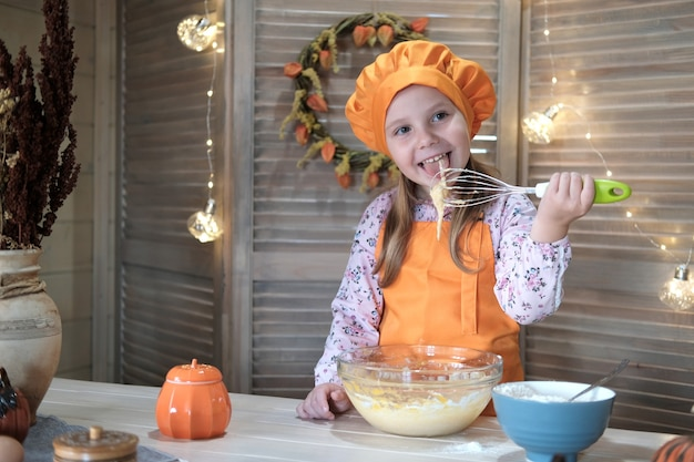 Ragazza carina in un costume da chef sta cucinando la torta di zucca in cucina. il processo di preparazione della torta di zucca per il ringraziamento