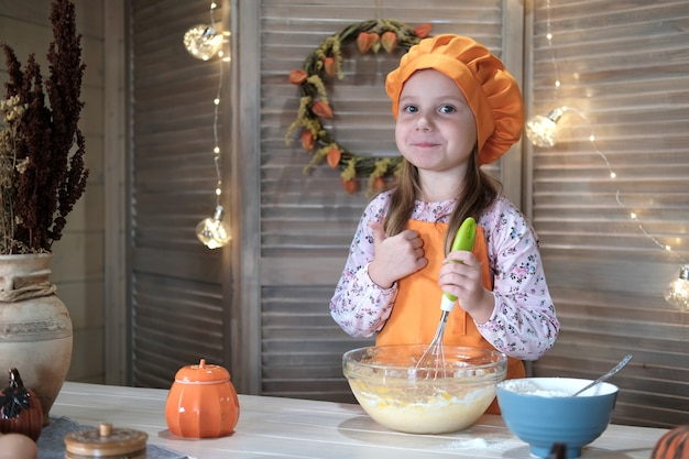 Ragazza carina in un costume da chef sta cucinando la torta di zucca in cucina. il processo di preparazione della torta di zucca per il ringraziamento Foto Premium
