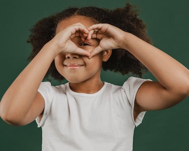 Ragazza carina bambino che fa una forma di cuore davanti al suo viso