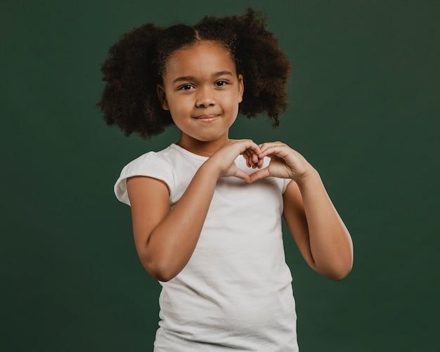 Ragazza carina bambino che fa una forma di cuore