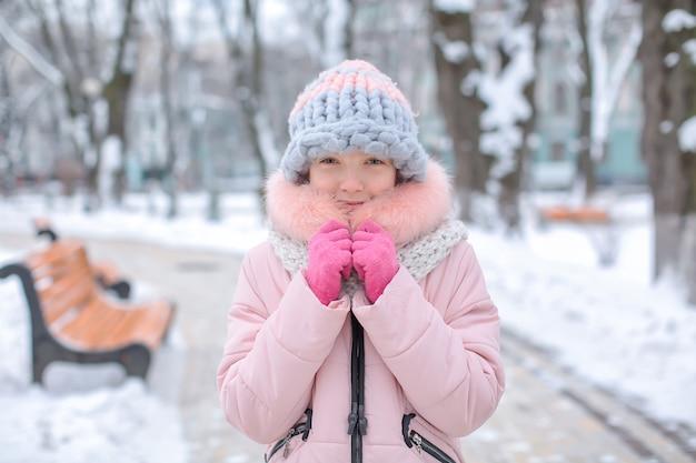 Ragazza carina nel parco nevoso freddo in vacanza invernale