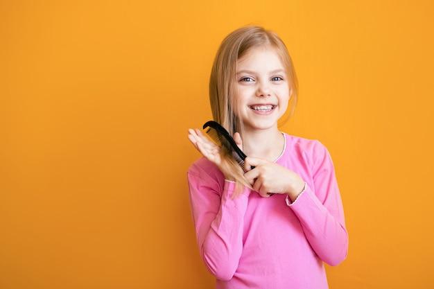 Ragazza sveglia che pettina i suoi morbidi capelli biondi sulla parete arancione