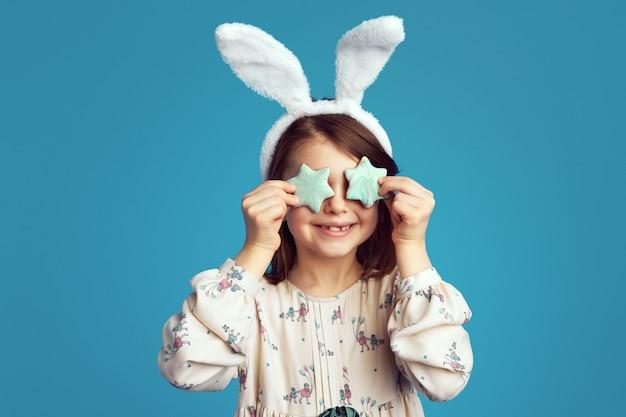 La ragazza carina si copre gli occhi con biscotti a forma di stella e indossa le orecchie da coniglio